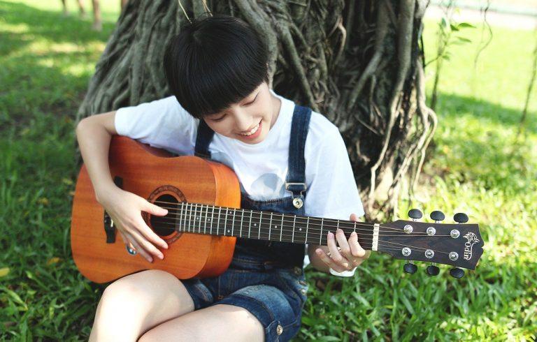 Foto: ragazza che studia la chitarra acustica