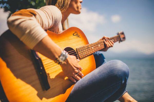 ragazza con chitarra in spiaggia